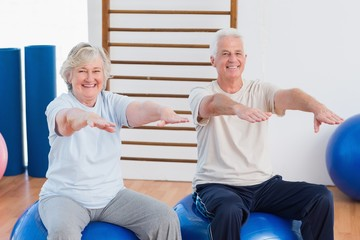 Senior couple with arms raised sitting on exercise ball