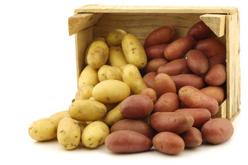 fresh yellow and red small potatoes in a wooden crate