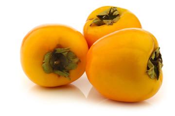 fresh kaki fruits on a white background