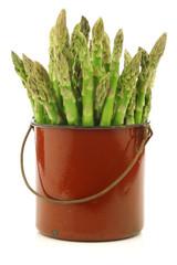 fresh green asparagus shoots in a brown enamel cooking pot