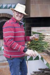 Hombre con cerveza preparando calçots