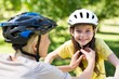 Mother attaching her daughters cycling helmet - 78778264