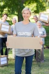 Happy volunteer blonde holding blank