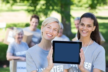 Happy volunteer friends showing tablet pc screen