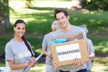 Happy volunteer man holding donation box