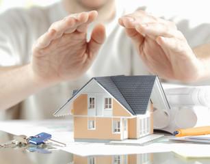 Conceptual Hands Covering Miniature Model Home