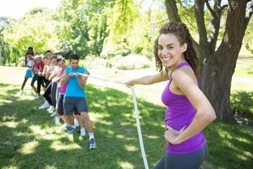 Fitness group playing tug of war