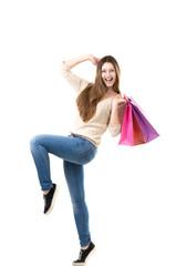 Beautiful teenage girl joyfully dancing with pink shopping bags