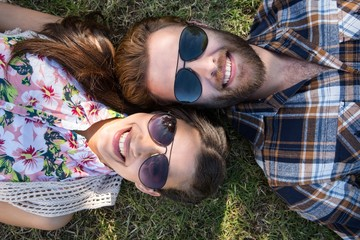 Young couple lying on grass smiling at camera