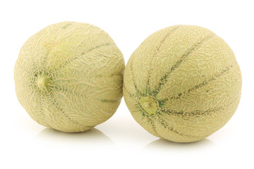two whole cantaloupe melons on a white background