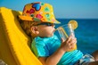 canvas print picture - Boy kid in armchair with juice glass on beach