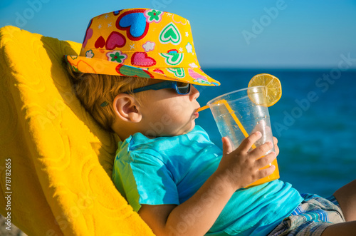 Boy kid in armchair with juice glass on beach - 78782655