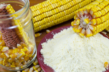 A jar with corn, flour and corn ear