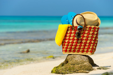 Summer beach bag with shell, towel on sandy beach