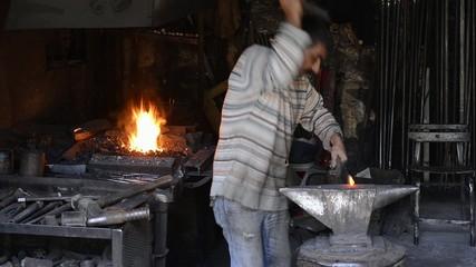 Blacksmith working in workshop