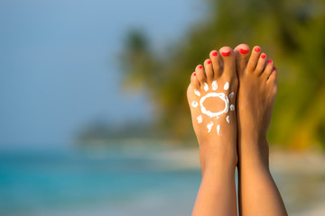 Woman foot with sun-shaped sun cream in the tropical beach conce