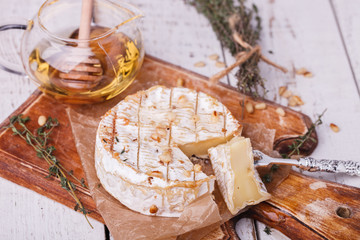 Baked Camembert with honey, pine nuts and thyme .