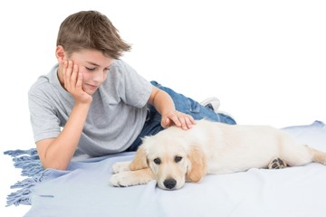 Boy stroking dog while lying on blanket