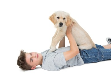 Boy holding puppy while lying over white background