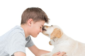 Puppy licking boy over white background