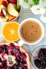 Roll with jam, sliced orange and coffee for breakfast