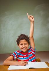 Little boy raising hand in classroom