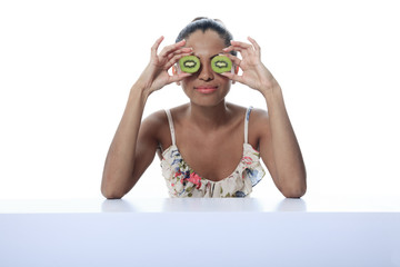 A mulatto person having two kiwi in front of the eye