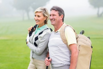 Golfing couple smiling and holding clubs