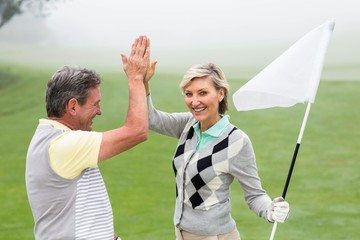 Golfing couple high fiving