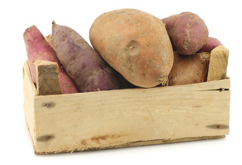 mixed sweet potatoes in a wooden crate on a white background
