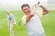 Happy golfer teeing off with partner behind him - 78785469