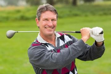 Cheerful golfer smiling at camera