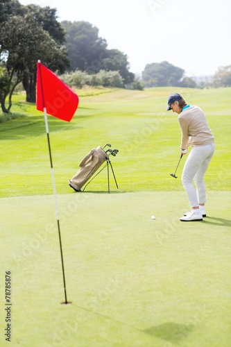canvas print picture Female golfer putting her ball