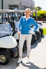 Female golfer beside golf buggy