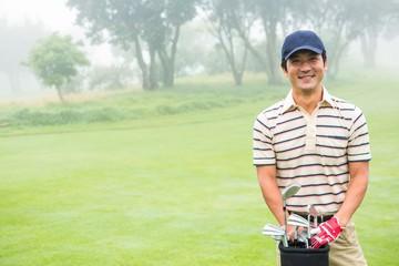Cheerful golfer smiling at camera holding golf bag