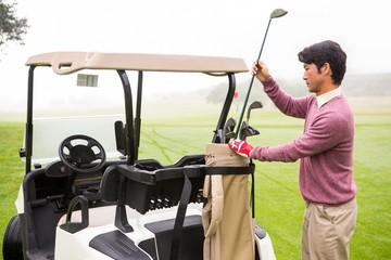 Golfer taking club in golf bag