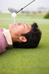 Golfer teeing off from lying man mouth