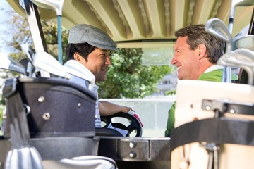 Golfing friends driving in their golf buggy