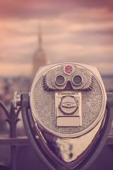 Retro style toned image of coin operated binoculars viewing NYC