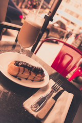 Retro style Italian chocolate eclair and latte at outdoor cafe