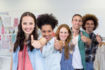 Confident fashion designers gesturing thumbs up