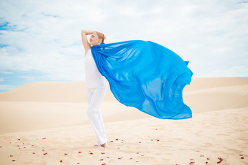 Young woman with flying blue scarf