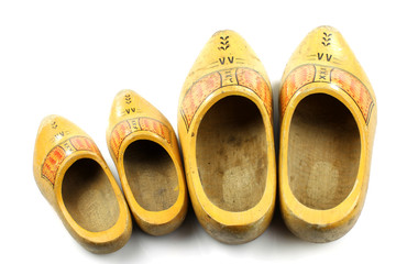 Old and young two pairs of traditional Dutch yellow wooden shoes
