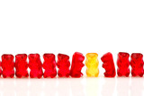 row of red gummy bears and a yellow one isolated on white