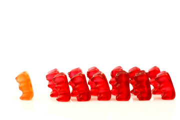 row of red gummy bears and one in front  on a white background