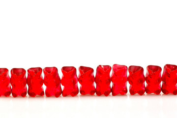 row of red gummy bears  on a white background