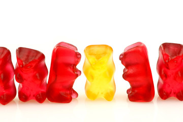 row of red gummy bears and a single yellow one on a white backgr