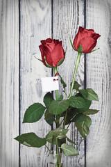 zwei rote Rosen mit Zettel