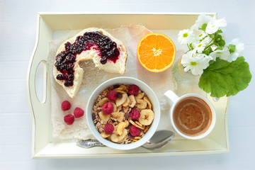 Tray with cereals, bread with jam and cup of coffee