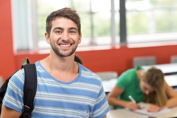 Happy male student standing in the classroom